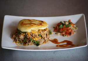 Homemade Venezuelan Arepa filled with Roasted Pork and Cheese. Sides of Pico de Gallo and Scratch Sauce